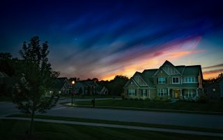 """alt=""""Green houses along the hi way wwith some trees and a lamp post and a blue hue skies."""""""